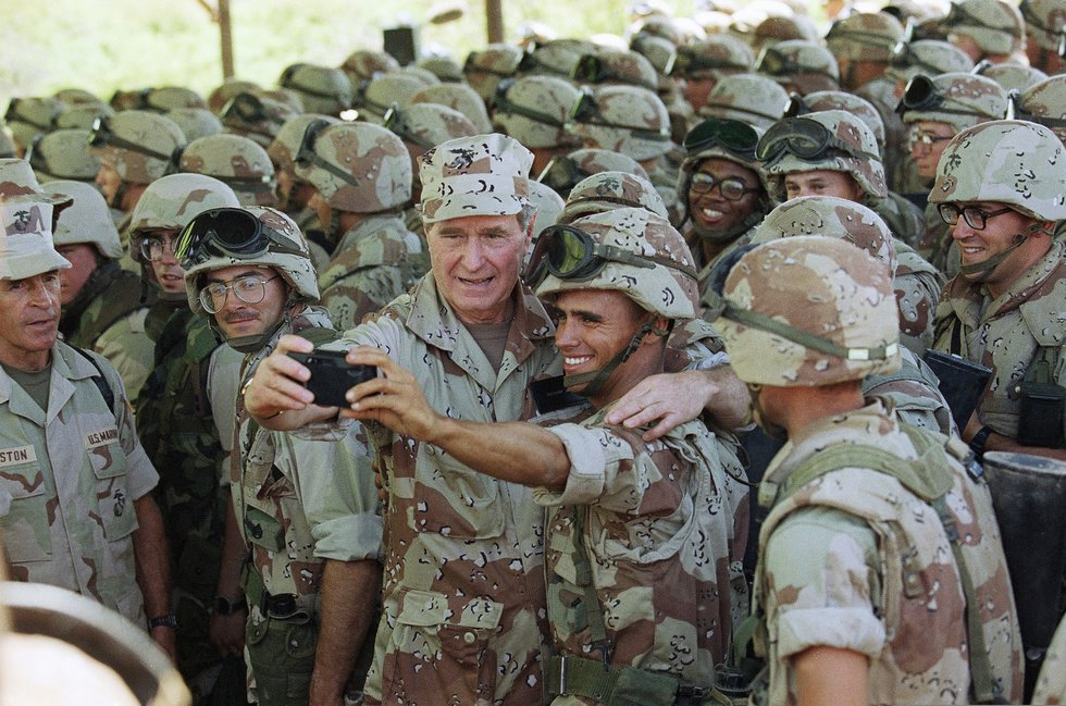 In this Jan. 1, 1993, photo, President George H.W. Bush holds a camera at arm's length for a...