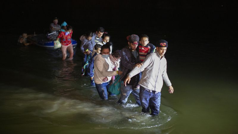 Migrant families, mostly from Central American countries, wade through shallow waters after...