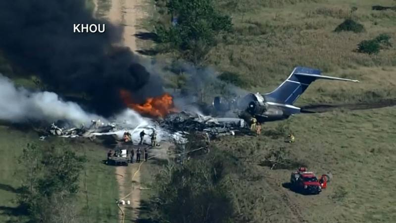 The crash site appears to be a field near the Houston Executive Airport. Firefighters are...