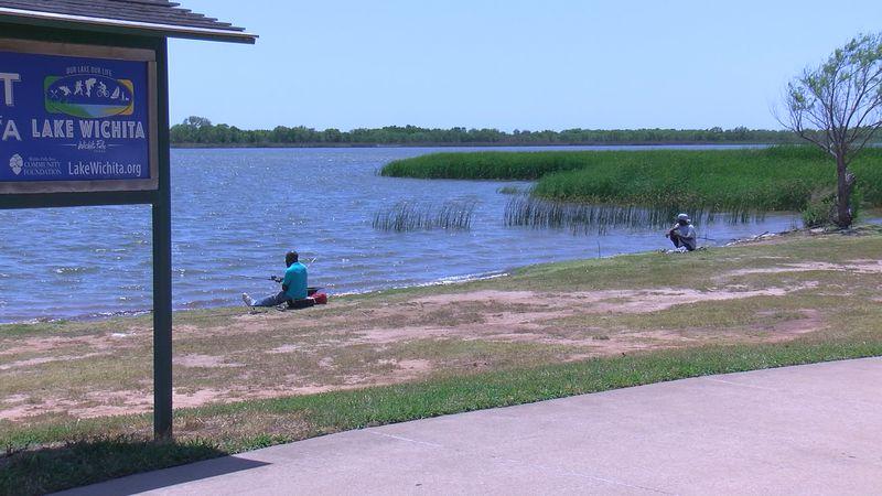 People sit along the bank of Lake Wichita fishing.