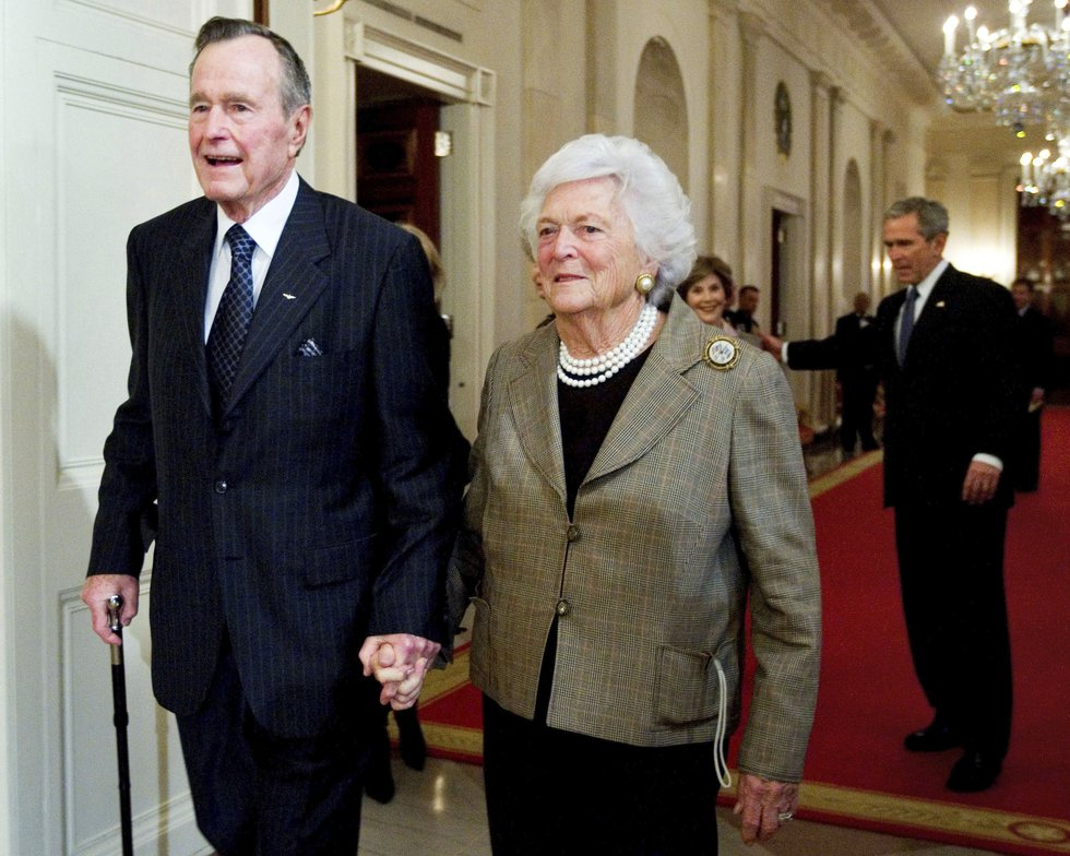 In this Jan. 7, 2009, photo, former President George H. W. Bush, left, walks with his wife,...