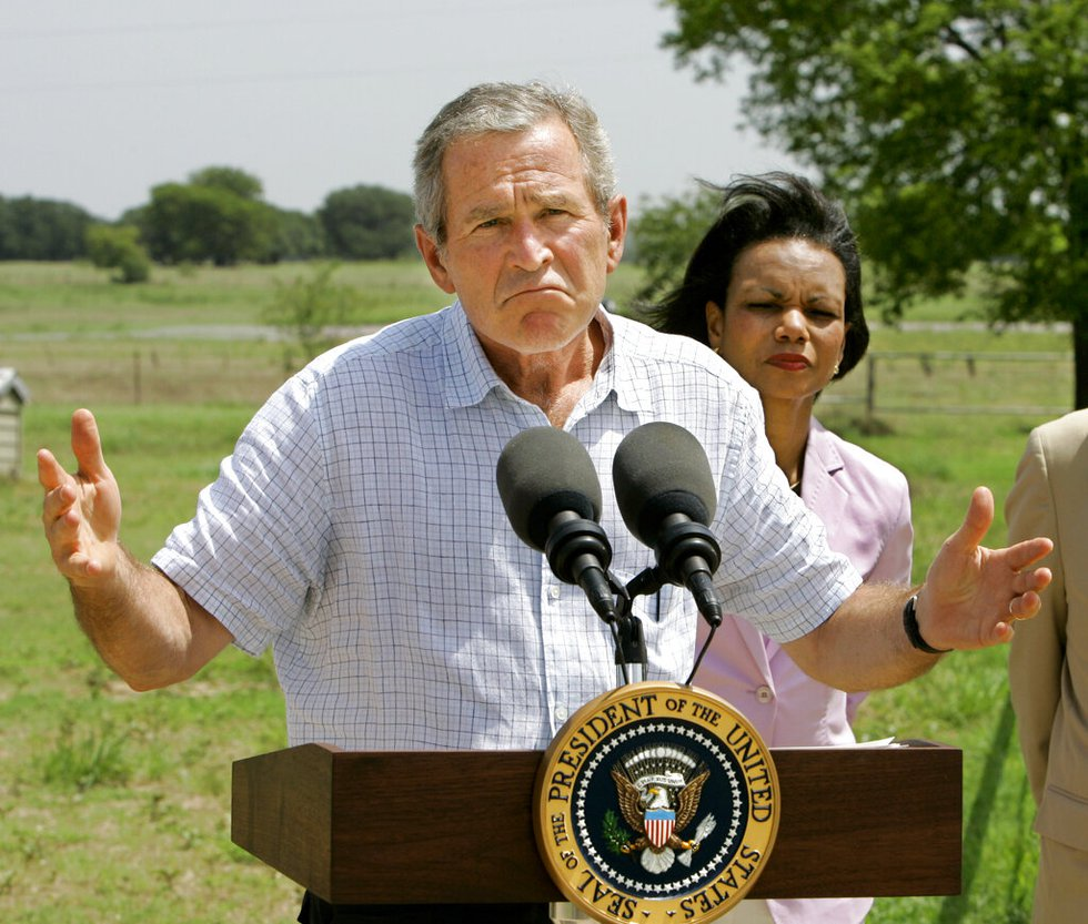 President Bush, joined at right by Secretary of State Condoleezza Rice, talks to reporters...