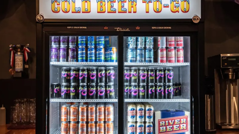Beer sits in a cooler behind the bar at Hops and Grain Brewery in Austin.