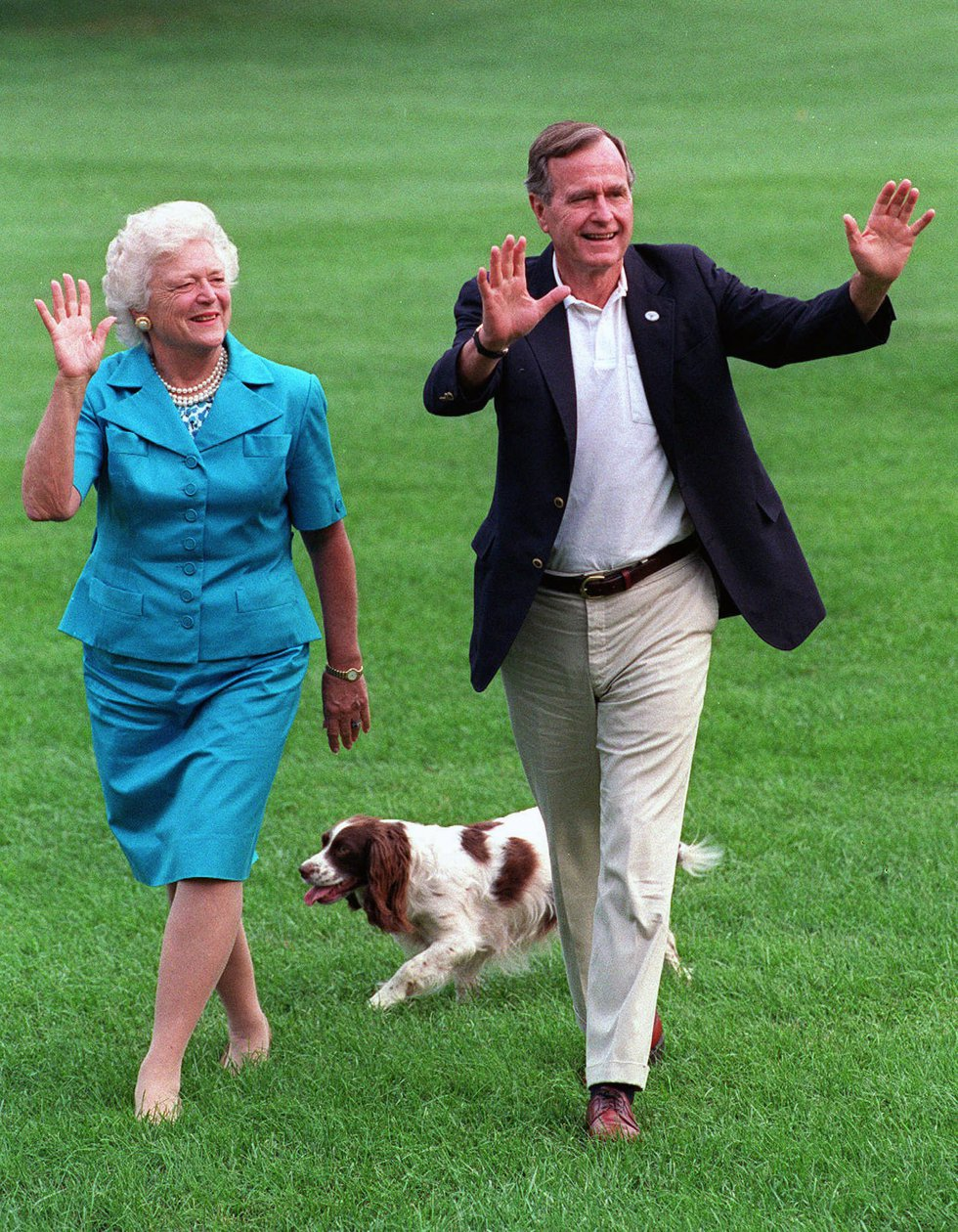 In this Aug. 24, 1992, photo, President George H.W. Bush and first lady Barbara Bush walk with...