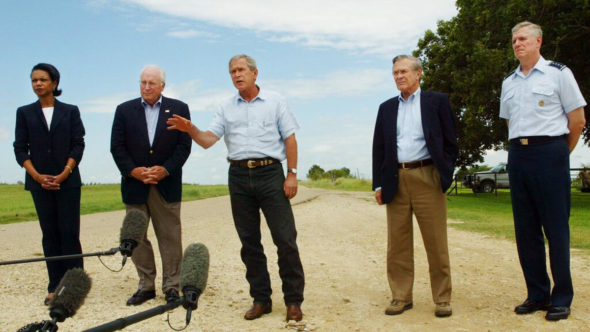 President Bush, center, answers questions from the media while standing with, from left to...