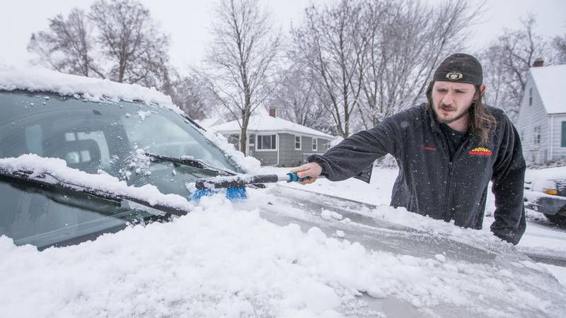 Patrick Kaczmarek, of South Bend, Ind., clears snow off his car on Monday, Nov. 26, 2018,...