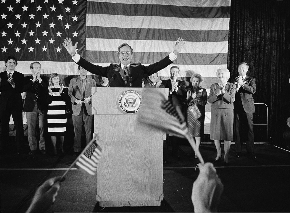 In this Nov. 7, 1984 photo, flag-wavers greet Vice President George Bush after he was...